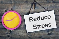 Reduce Stress sign on wooden table Stock Photos
