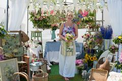 A pretty laughing female florist holding a bunch of flowers standing in front Stock Photos