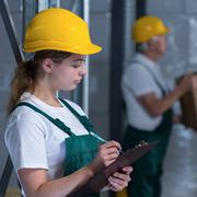 Female manufacturing labourer holding clipboard and noting Kuvituskuvat