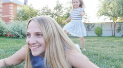 Happy little girl and her mother having fun outdoors on the green grass Stock Footage