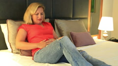 Woman having a painful stomach ache Lying on a bed, hands on abdomen 3 Stock Footage