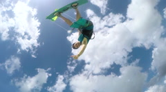 SLOW MOTION: Cheerful kite surfer jumping high over camera showing shaka sign Stock Footage