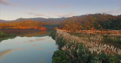 Aerial of reflective mirror on a lake during sunrise in the Coromandel Peninsula Stock Footage
