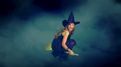 Beautiful young witch flying on broom breaking through cloud mass. Stock Footage
