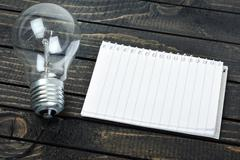 Notepad and bulb on table Stock Photos