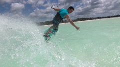 SLOW MOTION CLOSEUP: Surfer doing kitesurfing turn splashing sea water drops Stock Footage