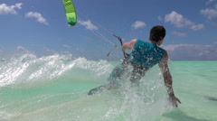 SLOW MOTION CLOSE UP: Happy smiling surfer kiteboarding in exotic island lagoon Stock Footage
