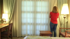 Woman opening curtains in a bedroom Stock Footage