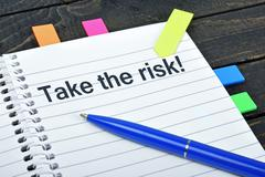 Take risk word on notepad Stock Photos