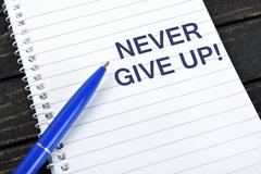 Never Give Up text on notepad Stock Photos
