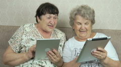 Two old women holding the silver digital tablets Stock Footage