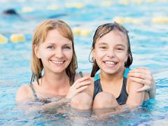 Mother and daughter in pool Kuvituskuvat