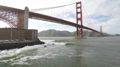 Pan up from Surfers shredding to the Golden Gate bridge. Stock Footage