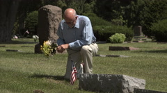 Man kneeling at a grave holding flowers Stock Footage