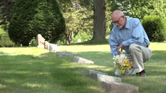Man kneeling at grave with flowers Stock Footage