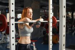 Young strong girl do squats with a barbell Stock Photos