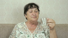 Elderly woman smiles, drinks water, shows thumb up Stock Footage