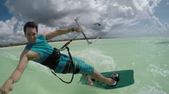 SLOW MOTION: Happy kiter kiteboarding past the camera showing shaka surf sign Stock Footage