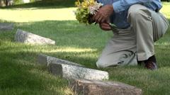 Man placing flowers on a grave, medium shot Stock Footage