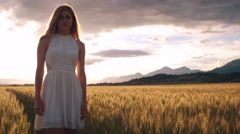 Jib shot - Young woman standing in the wheat field and looking into the camera Stock Footage