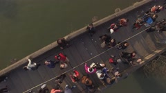 Aerial over head move up shot of old style bridge full of people Stock Footage