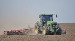 Farm tractor handles earth on field Stock Footage