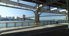 Walkers and Joggers on the East River Bikeway with Brooklyn Bridge in Distance   Stock Footage