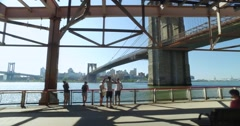 Profile View Riding on East River Bikeway with Brooklyn Bridge in Distance   Stock Footage