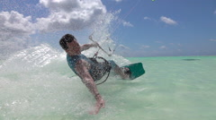 SLOW MOTION CLOSE UP: Cheerful surfer has fun kiteboarding in exotic island sea Stock Footage