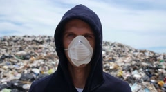 Man in Mask Looking in Camera on Landfill Site. Pollution Stock Footage