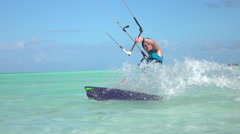 SLOW MOTION: Happy smiling surfer guy kiteboarding in perfect tropical lagoon Arkistovideo
