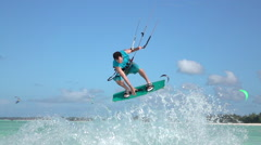 SLOW MOTION: Young kite surfer has fun jumping tricks in tropical ocean Stock Footage