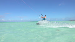SLOW MOTION: Happy smiling surfer has fun kiteboarding in blue tropical lagoon Stock Footage