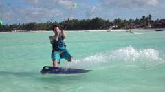 SLOW MOTION: Happy smiling surfer has fun kiteboarding on amazing exotic island Stock Footage