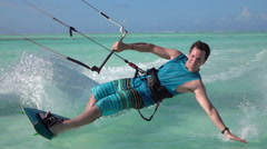 SLOW MOTION: Young surfer man kitesurfing in beautiful turquoise ocean lagoon Stock Footage