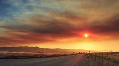 Smoke cloud from wildfire fire over freeway in California at sunset. Timelapse. Stock Footage
