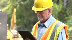 Man using his tablet/ipad on a construction site Stock Footage