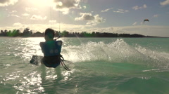 SLOW MOTION: Young surfer man kitesurfing in beautiful turquoise ocean at sunset Stock Footage