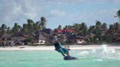 SLOW MOTION: Kite surfer kiteboarding on stunning Zanzibar white sand surf beach Stock Footage