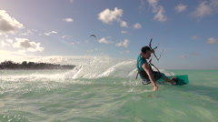SLOW MOTION: Young surfer man kiteboarding in tropical island lagoon at sunset Stock Footage