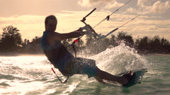 SLOW MOTION: Happy smiling surfer man kiteboarding in tropical lagoon at sunset Stock Footage