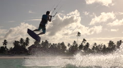 SLOW MOTION: Extreme surfer man kiteboarding and jumping high at sunset Stock Footage