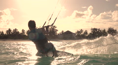 SLOW MOTION: Extreme surfer kiteboarding and jumping high at summer sunset Stock Footage