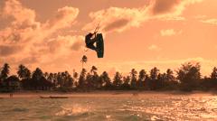 SLOW MOTION: Extreme kiteboarder jumping high at golden orange sunset Stock Footage