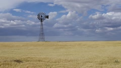 Windmill Spinning in grain field Stock Footage