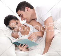 Woman reading dairy, affectionate man trying to kiss her Stock Photos