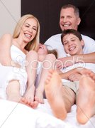 Loving family of four having fun and looking at you - stock photo