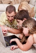 Domestic family of four lying and working with laptop Stock Photos