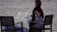 4K classy woman alone at restaurant dinner table, sea view at dusk Stock Footage