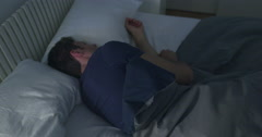 Dreaming man turns as he sleeps in double bed 4K Stock Footage